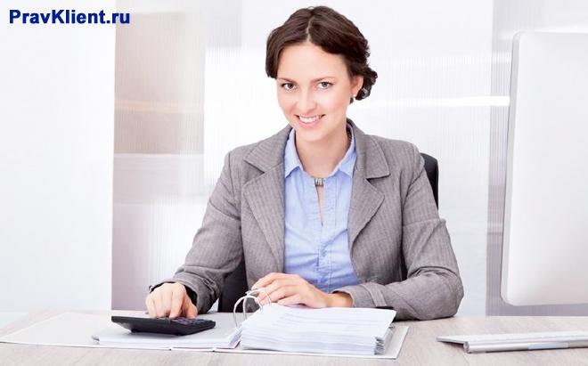 Молодая девушка сидит за своим рабочим местом в офисе