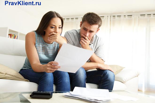 Семейная пара знакомиться с документами в своей гостиной