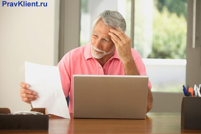 Мужчина читает лист бумаги сидит за ноутбуком