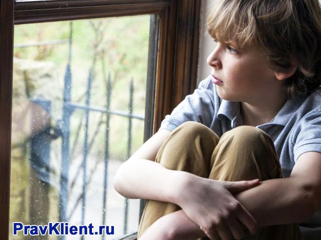Мальчик сидит на подоконнике и смотрит в окно