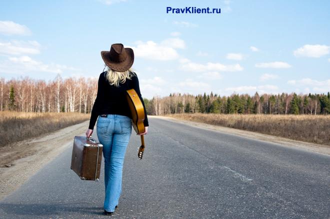 Девушка идет с чемоданом в руке по дороге