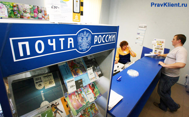 Мужчина покупает корреспонденцию в отделении Почты России