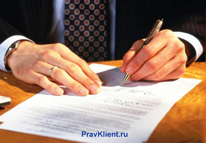 Бизнесмен подписывает бумагу