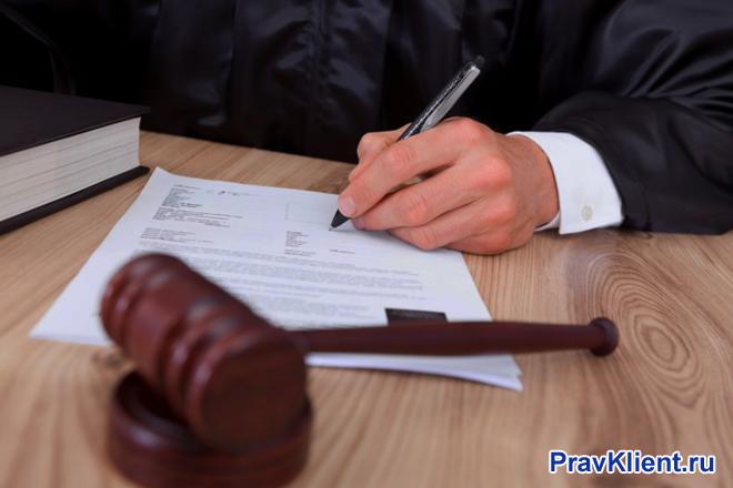 Судья пишет на листке бумаги