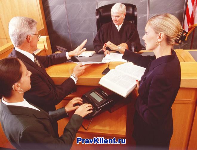 Судья разговаривает с сторонами судебного процесса