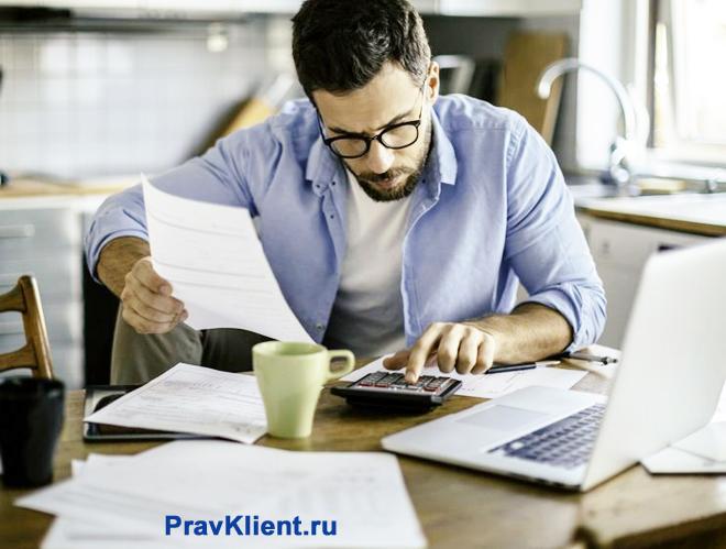 Мужчина читает документы и считает на калькуляторе