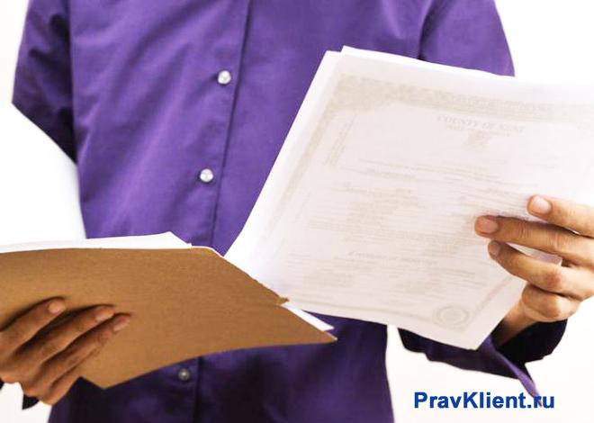 Мужчина в сиреневой рубашке читает документы