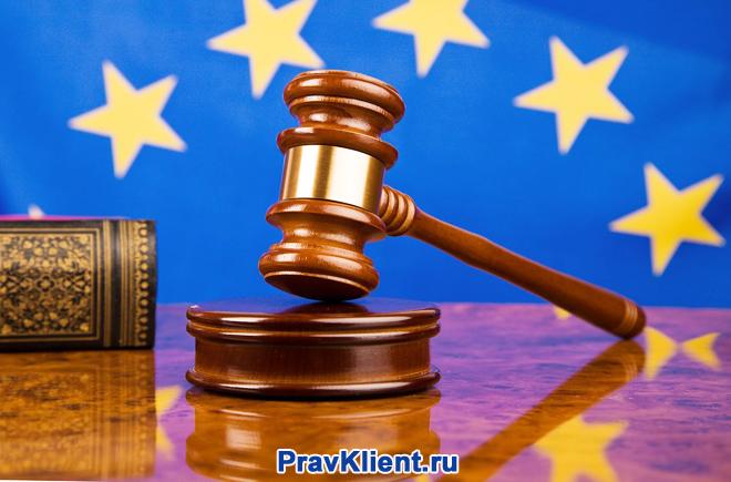 Деревянный молоточек на фоне флага ЕС