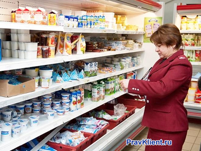 Сотрудница Роспотребнадзора проверяет молочную продукцию в магазине