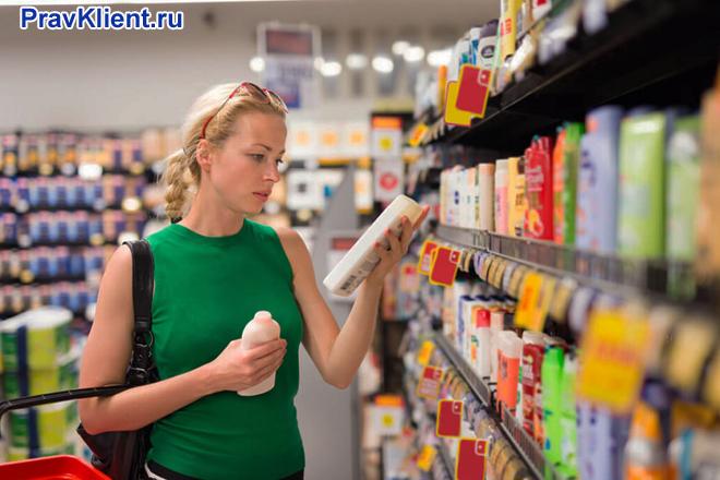 Девушка выбирает товар в продовольственном магазине