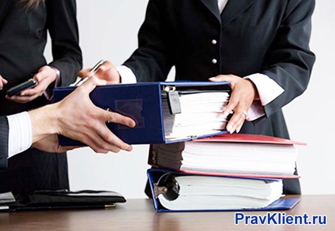 Офисные работники раскладывают папки с документами