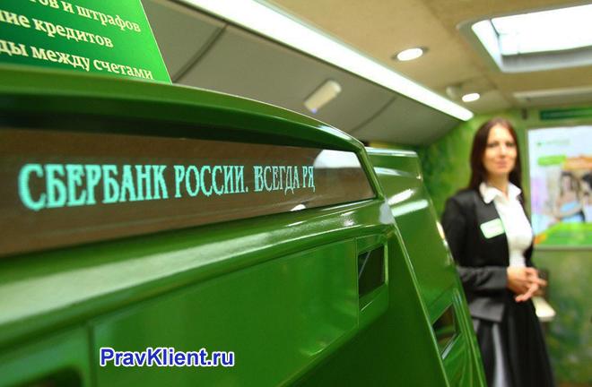 Сотрудница Сбербанка стоит около банкомата