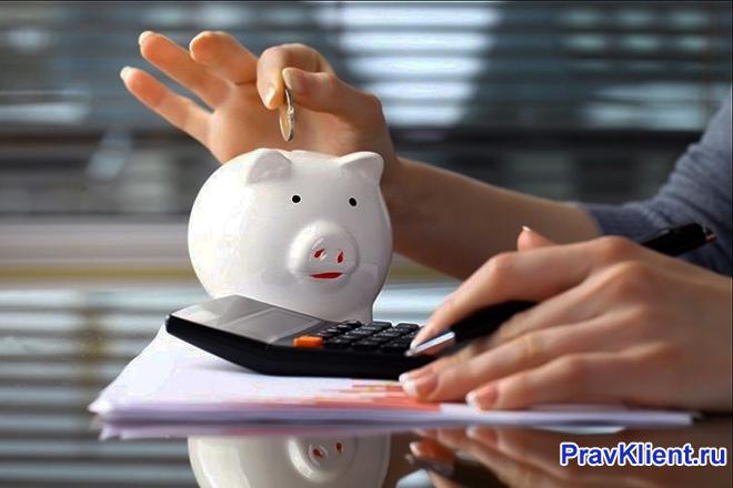 Девушка считает на калькуляторе и складывает монеты в копилку