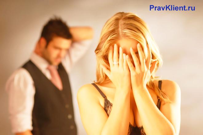 Расстроенная женщина стоит на фоне мужчины