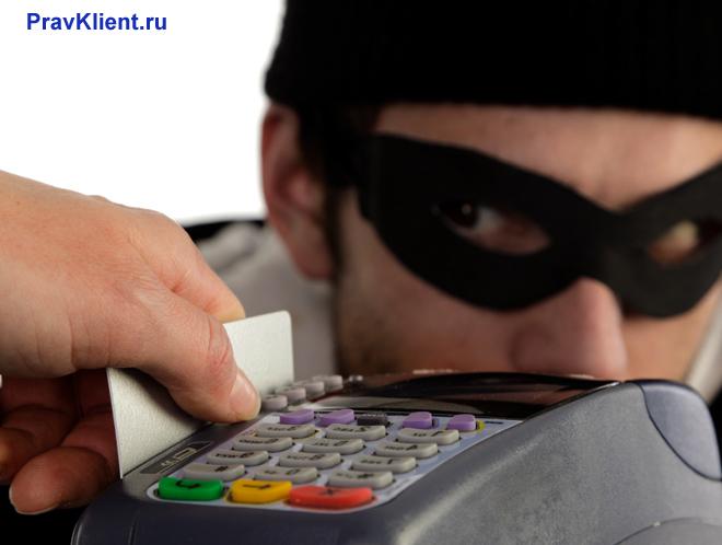 Мужчина в черной маске следит за банковским терминалом