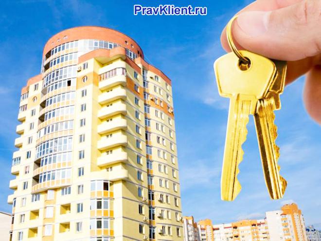 Человек держит в руке связку ключей на фоне многоэтажного дома