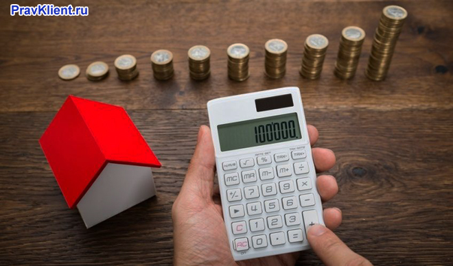 Девушка считает на калькуляторе, на столе стоит домик и стопки монет