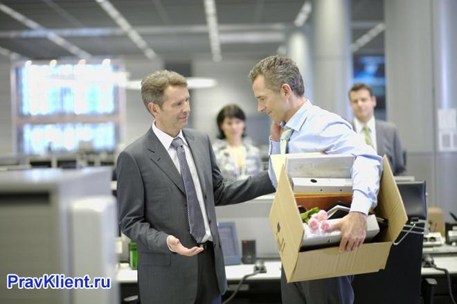 Мужчина стоит с собранными вещами в офисе, коллеги его провожают