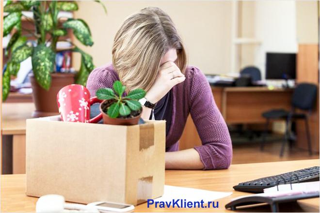 Расстроенная девушка сидит за столом, рядом стоит коробка с вещами
