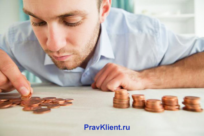 Мужчина считает монеты на столе