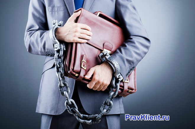 Бизнесмен держит портфель в руках