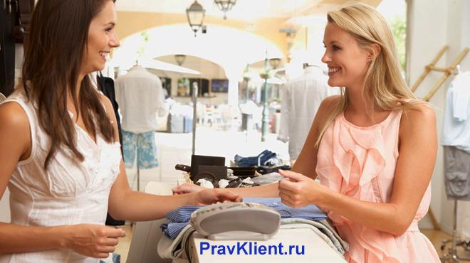 Девушка расплачивается за покупки в магазине одежды