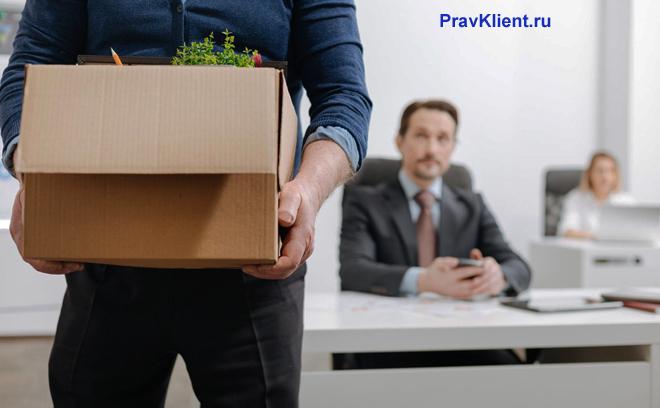 Мужчина несет коробку с вещами на фоне коллег