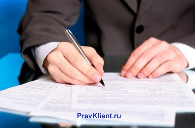 Мужчина в деловом костюме делает записи в листах бумаги