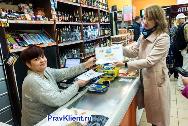 Девушка расплачивается на кассе супермаркета