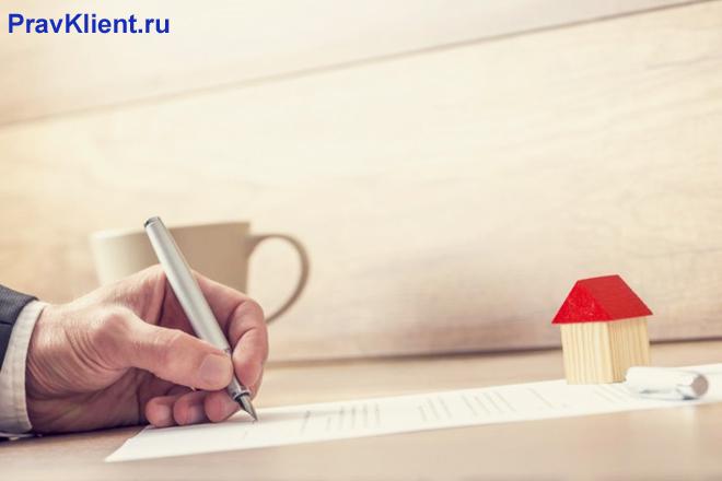 Мужчина пишет заявление, на столе стоит игрушечный домик и кружка