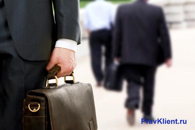 Бизнесмен идет по улице с портфелем