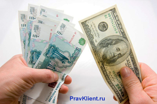 Мужчина держит в руках российские рубли и американские доллары