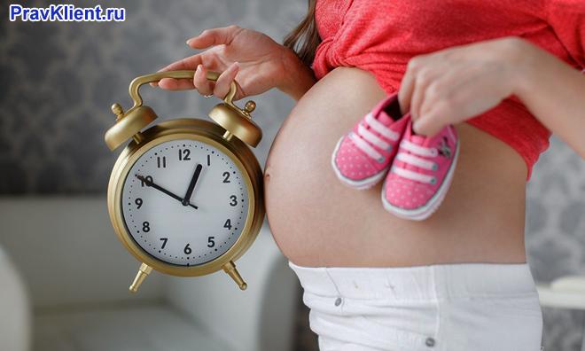 Беременная женщина держит пинетки, будильник