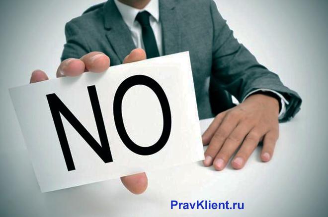 Бизнесмен держит в руке записку со словом НЕТ