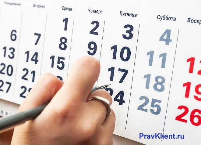 Человек отмечает дату на листке календаря
