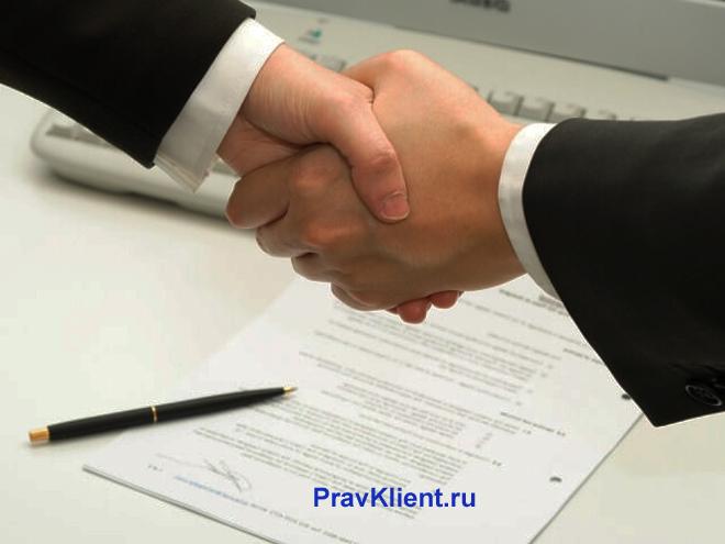 Мужчины в деловых костюмах жмут друг другу руки