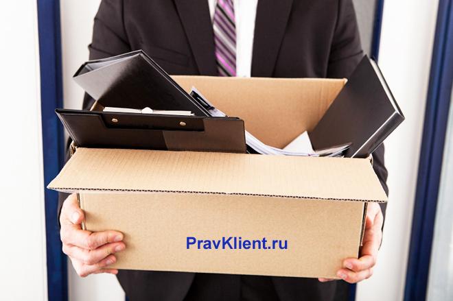 Мужчина несет в руках коробку с ноутбуком