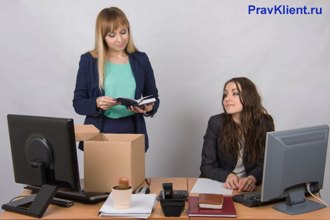 Девушка собирает вещи со своего рабочего стола, рядом сидит коллега