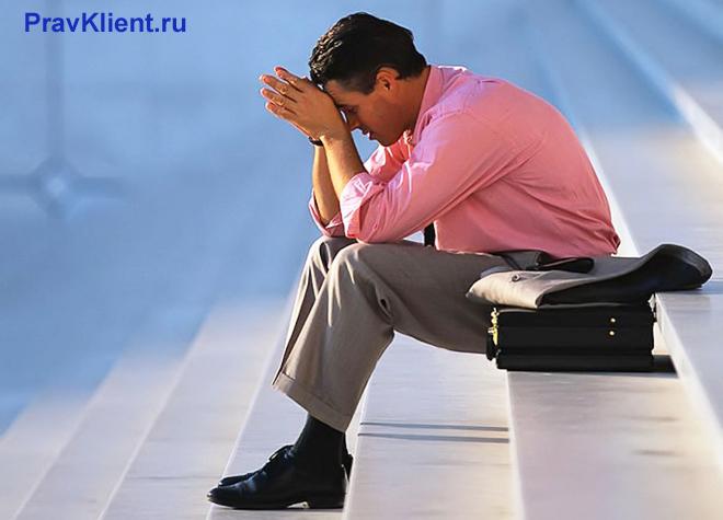 Расстроенный мужчина сиди на ступеньках лестницы