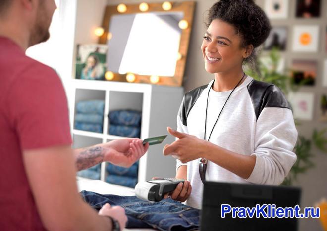 Мужчина расплачивается кредитной картой за покупку