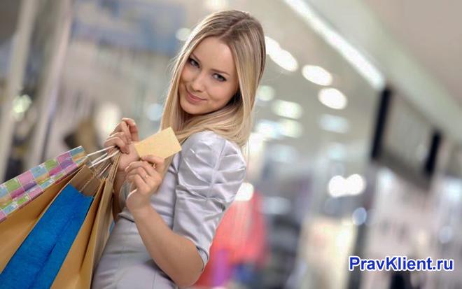 Девушка держит в руке пакет с покупками