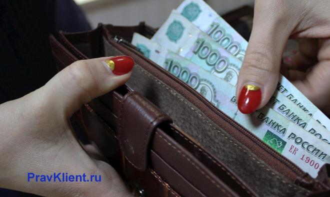 Женщина достает из кошелька тысячные купюры