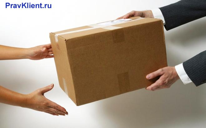 Передача картонной коробки из рук в руки