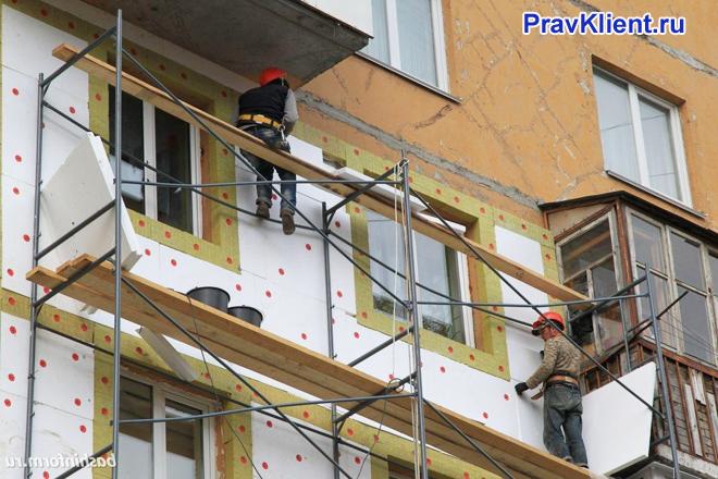 Рабочие утепляют стены дома