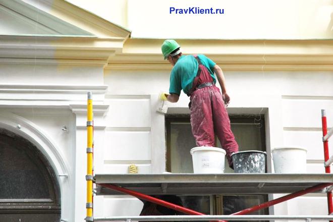 Рабочий шпаклюет фасад дома