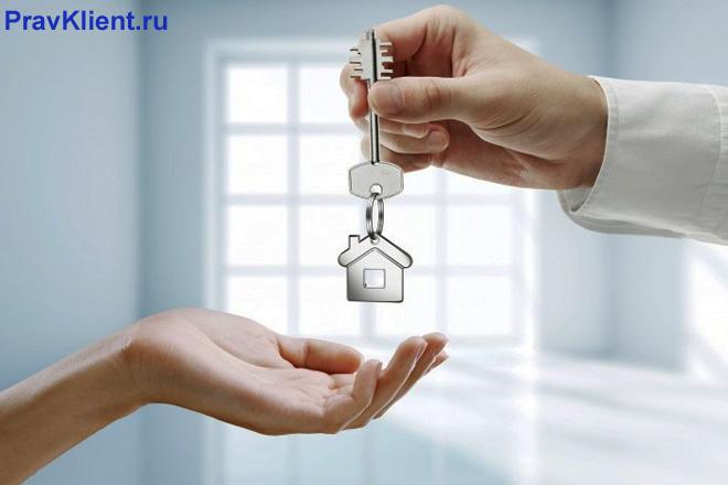 Мужчина отдает женщине ключи с брелком в виде домика