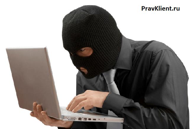 Мужчина в черной маске за ноутбуком