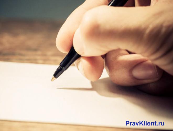 Мужчина пишет жалобу на листке бумаги