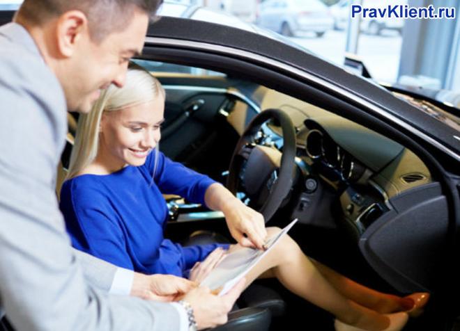 Девушка подписывает документы на покупку автомобиля