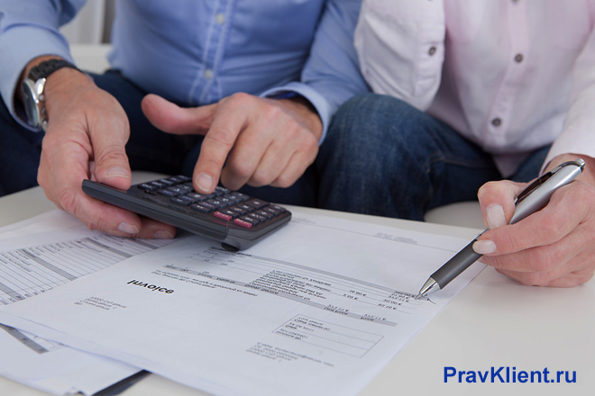 Двое мужчин ведут расчеты на калькуляторе, на столе лежат документы